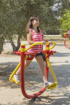 Young Girl using an exercise machine in a park Stock Photo