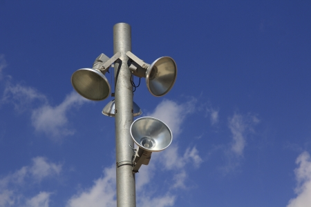 modern pole with spotlights and blue sky with clouds behind photo