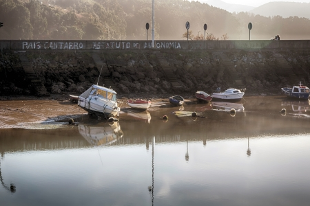 small boats for fishing and recreation in a dam at low tide
