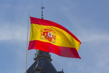 Spanish flag waving in the wind against a blue sky with clouds photo