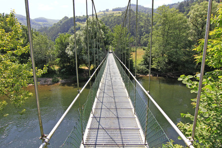 narrow suspension bridge over a river with lots of greenery photo