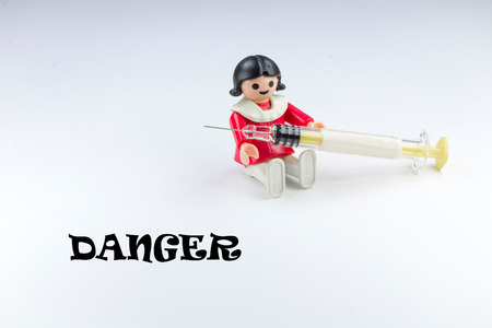 Doll playing with a syringe and warning sign photo