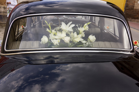 shinny: flowers decorating an old black luxury car