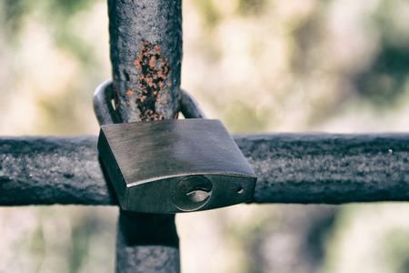 keep gate closed: Old padlock on iron bars Stock Photo