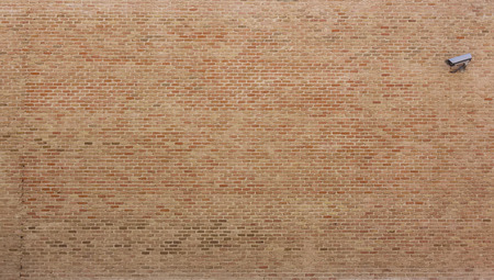 Background of red bricks wall with a surveillance camera in one hand photo
