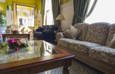 elegant antique sofas, glass table with flowers and relaxing