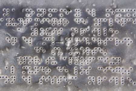 Braille letters on an old metal plate photo