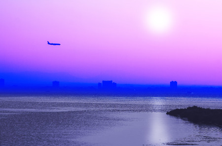 Romantic sunset with airplane in the sky in pink and blue photo