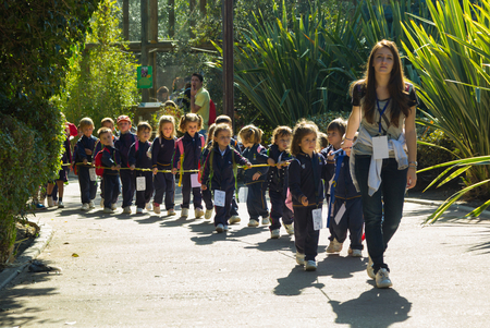 MADRID,SPAIN - October, 31:Long row of children subject to a rope to walk along missed a teacher by beautiful gardens  on October, 31, 2014 in Madrid, Spain Editorial