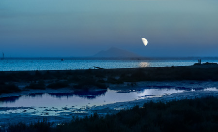 horizon over water: night by the sea with large moon Stock Photo