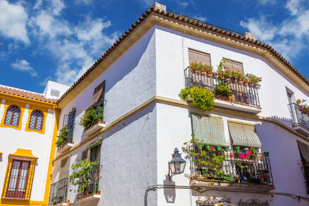 old house window: Typical windows with grilles and decorative flowers in the city of Cordoba, Spain