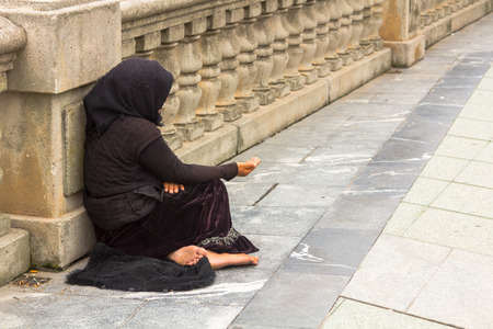 Poor woman begging in the street Stock Photo