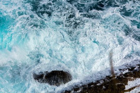 waves crashing: ocean waves crashing on the rocks with white foam