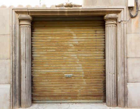 louvered: Old wooden louvered door between columns Stock Photo