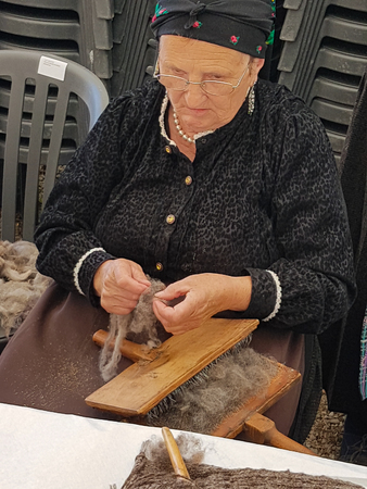 carding: Ainsa 10 September 2017: Spinner with traditional Pyrenees costume cardinating traditional wool in Ainsa Spain. Editorial