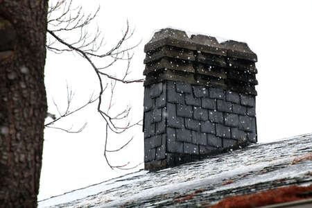 chimney on a slate roof during a snowfall