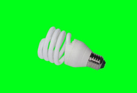 Energy-saving fluorescent electric light bulb on a green background. Stock Photo