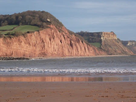 Beach with red cliffs behind at Sidmouth, Devon, England, UK