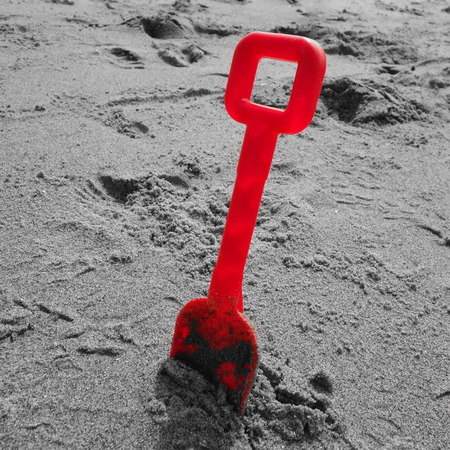 spade: Red Plastic Spade on Beach