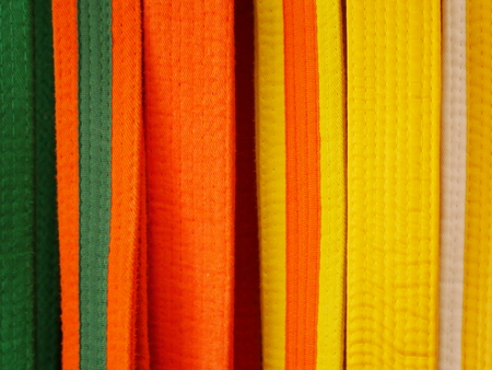 Closeup of martial arts belts for karate or kickboxing - white with yellow tag, yellow, yellow with orange tag, orange, orange with green tag, green