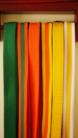 Martial arts belts for karate or kickboxing hanging on display - white with yellow tag, yellow, yellow with orange tag, orange, orange with green tag, green 版權商用圖片