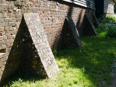 Row of brick buttresses holding up a wall
