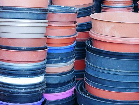 Multiple stacks of round multi coloured plastic flower pots Stock Photo