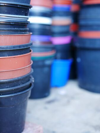 Stack of round multi coloured plastic flower pots with more stacks In background