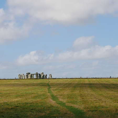 Path leading towards Stonehenge with white clouds in blue sky Stock Photo