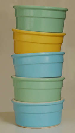 Stack of blue green and yellow pastel coloured ramekin bowls Stock Photo