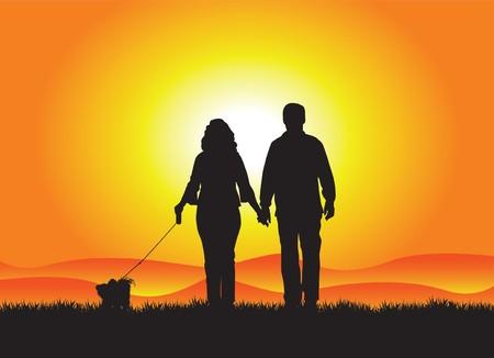 perro de la pareja caminando en la puesta de sol