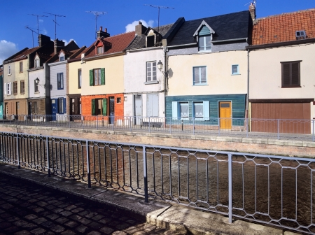 Houses next to canal or river. - amiens the canal de la somme, somme department, picardy france photo