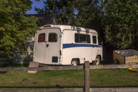 an old ambulance converted into a camper van standing unused in a garden photo