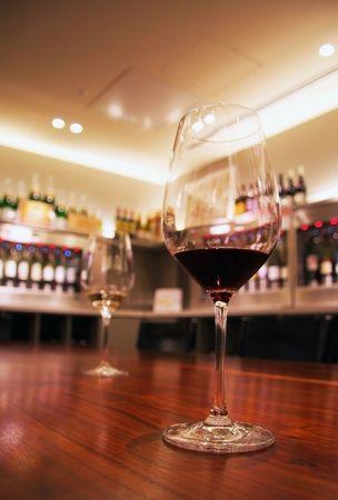 Twee glazen wijn, rood en wit, ontmoeten elkaar op een eenzame tabel. Stockfoto