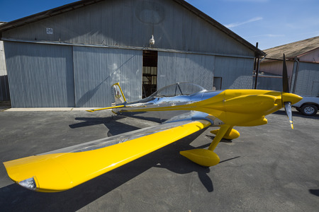 A plane in front of an old hangar