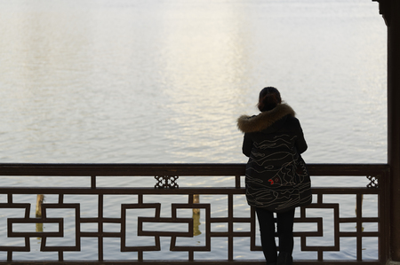 Silhouette of a woman gazing out over the water