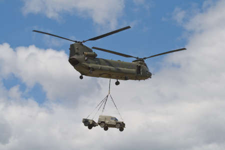 Farnborough, England, UK - July 24, 2010: British Army Boeing CH-47 carrying a Land Rover during Farnborough 2010 Airshow.