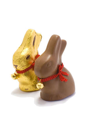 A golden and chocolate Easter bunny sit side by side on a white background  Stock Photo - 12955341
