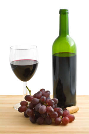 A glass and a bottle of red wine with grapes on a wooden table, isolated on a white bakground  photo