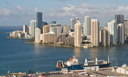 Miami, Florida, USA - May 4, 2012: The highrise condominiums and office blocks of Brickell Key form an impressive backdrop as a bulk cargo ship waits to be loaded at the start of another busy day at the Port of Miami.