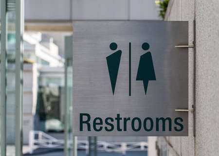 A modern public restrooms sign made from brushed metal attached to a concrete wall  photo