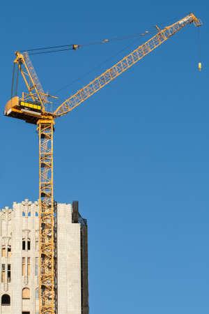 A tall, yellow construction crane being used on a re-development site. photo