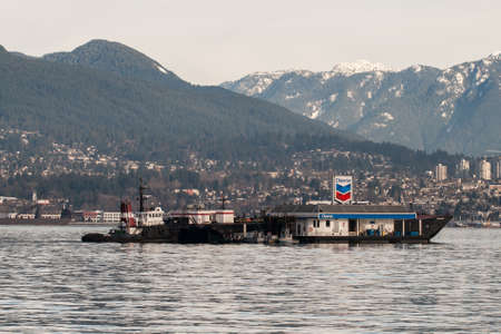 public company: Vancouver, BC, Canada - January 17, 2013: Vessels dock at a floating Chevron gasoline filling station in Coal Harbour, Vancouver, BC. In 2011 Chevron Corporation was named as the 16th largest public company in the world by Forbes Global.