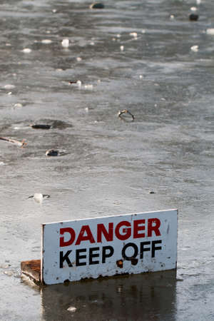 thaw: Danger Keep Off warning sign in the middle of a frozen lake