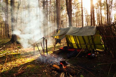 Campamento de Bushcraft primitivo con luz que entra a través del humo de la fogata. Foto de archivo