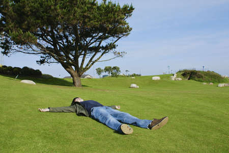 lied: youngster lied spread open on green grass on a sunny day  Stock Photo