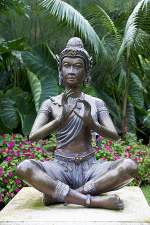 Buddha statue with vegetation background