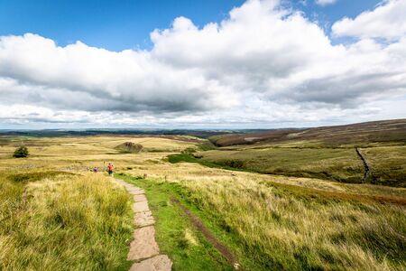 Walkers along a footpath over Haworth Moor. Yorkshire
