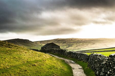A isolated barn with a path and wall. Malham. Yorkshire
