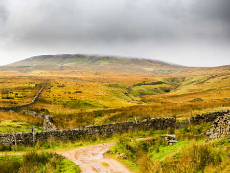 A dry stone wall terminates the old road with open moorland in front and mountains in the distance. Scar House. Nidderdale. Yorkshire Dales National Park